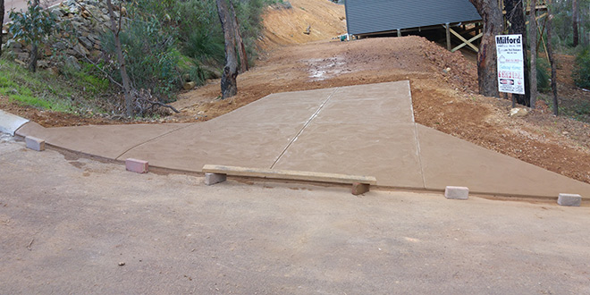 Peach coloured concrete crossover on a slope